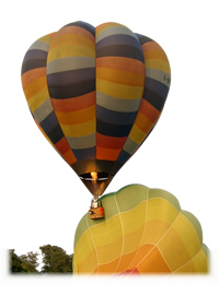 Click to Book a Hot Air Balloon Flight over Gloucestershire. (Photo of two hot air balloons, one is being inflated and the other has just taken off.)